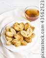 Puff pastry hearts on white plate with Cup of tea 43562523