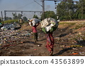 Indian woman carrying slum trash along the Indian capital Delhi railway track 43563899