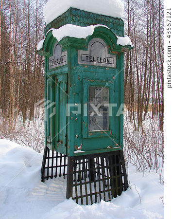Old telephone box in forest under snow 43567121