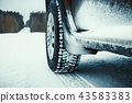 Car tires covered with snow on winter road. 43583383