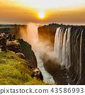 Victoria falls sunset with orange sun and tourists 43586993
