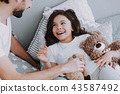 Cute Young Daughter Lying in Bed Playing with Dad 43587492