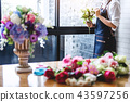 Arranging artificial flowers vest decoration at home, Young woma 43597256