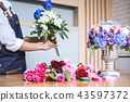 Arranging artificial flowers vest decoration at home, Young woma 43597372