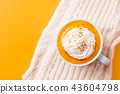 Pumpkin latte with spices. Boozy cocktail with whipped cream on knitted scarf. Orange background. 43604798