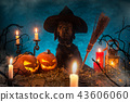Black dog with Halloween pumpkins on wooden planks. 43606060