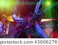 A rocker is playing guitar on stage. 43606276