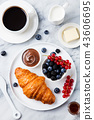 Croissant with berries, chocolate spread and butter, cup of coffee on a marble background. Top view. 43606695
