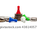 Red chess pawn on the top of coins 43614057