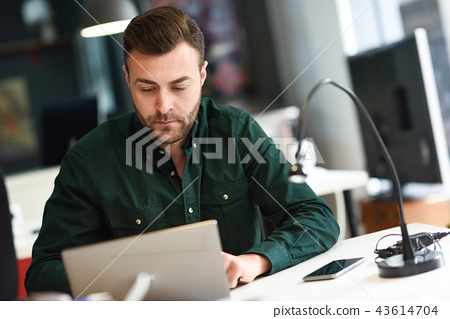 Young man studying with laptop computer on white desk. 43614704