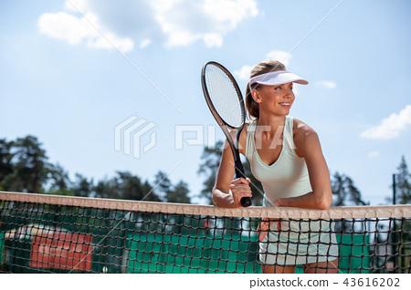 Happy woman is resting during break in tennis set 43616202