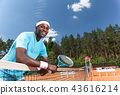 Cheerful guy is having good time during tennis game 43616214