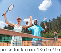 Exited couple is rejoicing at success during tennis match 43616216