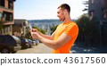 man with smartphone and earphones at san francisco 43617560