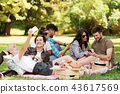 friends with smartphones on picnic at summer park 43617569