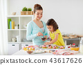 happy mother and daughter cooking cupcakes at home 43617626