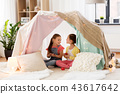 little girl playing tea party in kids tent at home 43617642