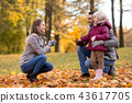 happy family with maple leaves at autumn park 43617705