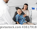 mother and son visiting dentist at dental clinic 43617918