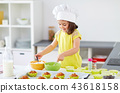 little girl in chefs toque baking muffins at home 43618158