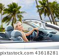 happy woman driving convertible car over beach 43618281