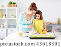 happy mother and daughter baking muffins at home 43618391