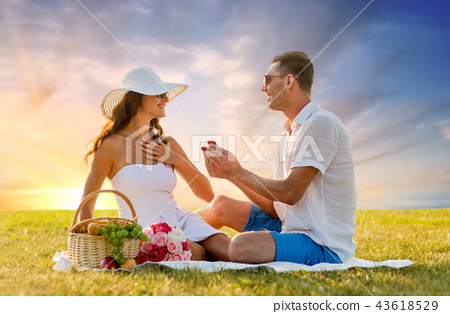 smiling couple with small red gift box at picnic 43618529