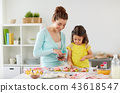 happy mother and daughter cooking cupcakes at home 43618547