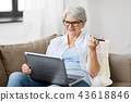 old woman with laptop records voice by smartphone 43618846