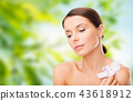 woman with orchid flower over green background 43618912