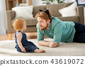 father wearing cat ears headband playing with baby 43619072