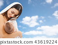 mother breast feeding baby over sky background 43619224