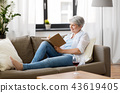 senior woman writing to notebook or diary at home 43619405
