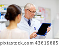apothecary and customer with tablet pc at pharmacy 43619685