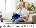 happy smiling senior woman reading book at home 43619933