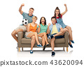 friends or football fans with soccer ball on sofa 43620094