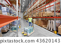 male worker with loader and clipboard at warehouse 43620143
