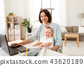 working mother with baby boy and laptop at home 43620189