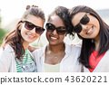 happy young women in sunglasses outdoors 43620221