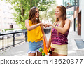 teenage girls with skateboards making fist bump 43620377