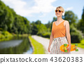 teenage girl with skateboard over summer park 43620383