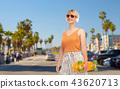 teenage girl with skateboard over venice beach 43620713