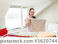 woman taking bath towels from drying rack at home 43620744