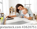 working mother with baby boy and laptop at home 43620751