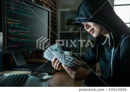 young female hacker holding cash in hands. 43620980