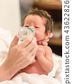Newborn baby drinking from a bottle 43622826