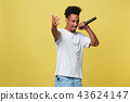 Young handsome African American Male Singer Performing with Microphone. Isolated over yellow gold 43624147