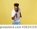 Young handsome African American Male Singer Performing with Microphone. Isolated over yellow gold 43624159