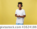 Young black man listening to music over his headphones. Isolated over yellow background. 43624186