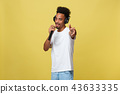 Young handsome African American Male Singer Performing with Microphone. Isolated over yellow gold 43633335